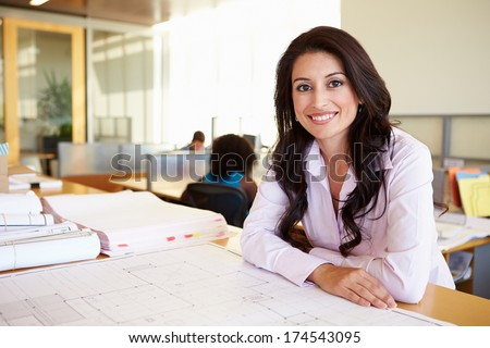 Female Architect Studying Plans In Office - stock photo