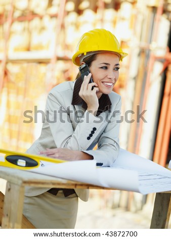female architect talking on mobile phone in construction site - stock photo