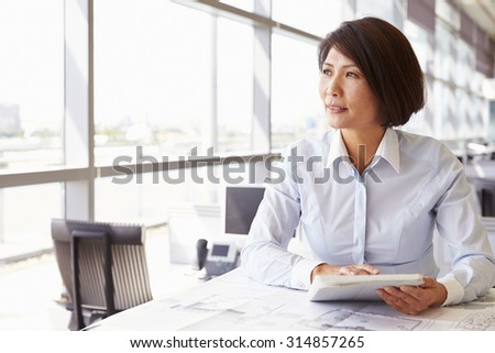 Female architect using tablet computer, looking away - stock photo