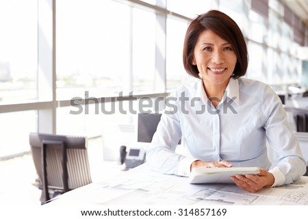 Female architect using tablet computer, looking to camera - stock photo