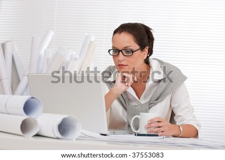 Female architect with laptop and coffee sitting at the office - stock photo