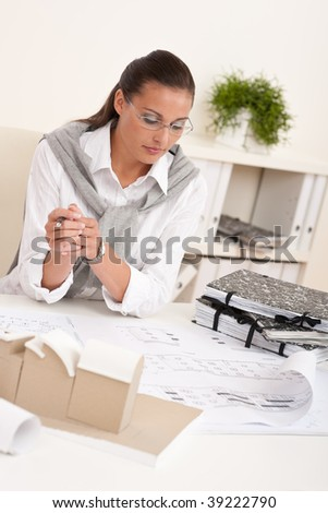 Female architect working with plans at the office holding pen