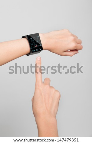 Female arm with a modern Internet Smart Watch on grey background. On the screen you can see a symbol for social networks. All Texts, Icons Interfaces of the Watch where created by myself. - stock photo