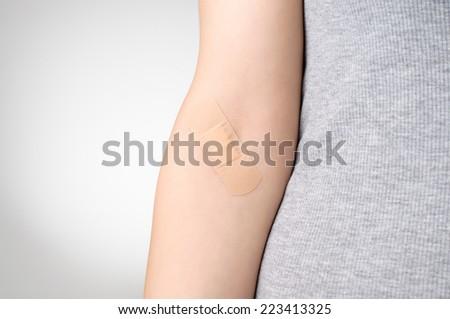 Female arm with adhesive bandage - stock photo