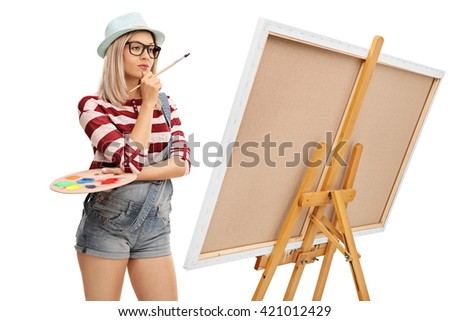 Female artist holding a paintbrush and a color palette and looking at a painting isolated on white background - stock photo