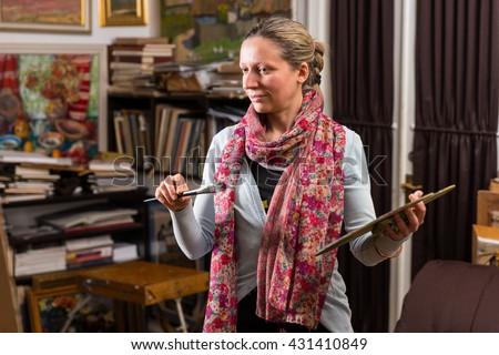 Female artist looking at her picture in her gallery holding a colorful artists palette and paintbrush in her hand - stock photo