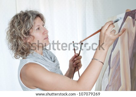 Female artist painting a picture. Against the background the studio. - stock photo
