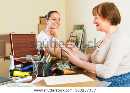 Female artist painting portrait of smiling young girl at art studio with pencil and paints