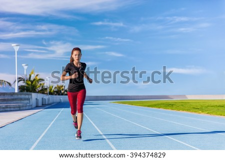 Female Asian athlete runner running on blue tracks at outdoor stadium in summer. Sporty woman jogging listening to music with earphones training cardio for weight loss success. Wellness and health. - stock photo