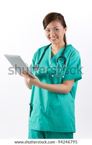 Female Asian doctor holding a digital tablet & wearing a green scrubs plus stethoscope. - stock photo