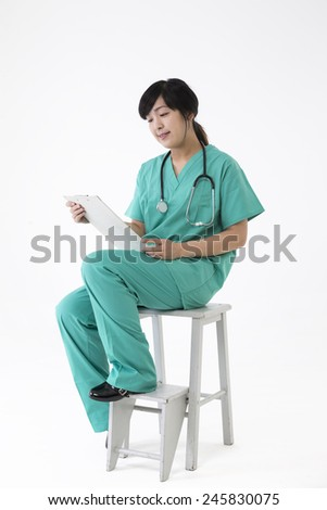 Female Asian doctor wearing a green scrubs reading a chart. Isolated on white. - stock photo