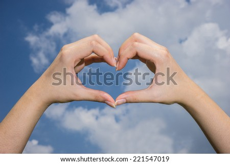 female asian hand form heart shape with sky background