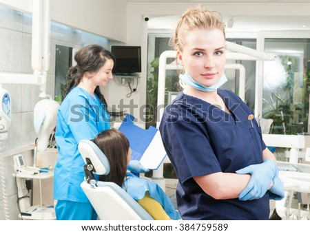 Female assistant with patient in backgound and dentist in front in dental clinic as coworkers and professional team concept