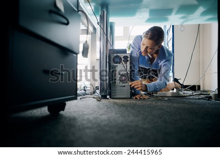 Female assistant working in office, plugging cables to computer and electronic equipment, messing around with wires. Copy space - stock photo