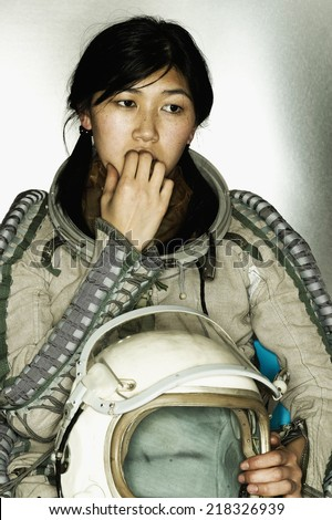Female astronaut holding a helmet biting her finger nails - stock photo
