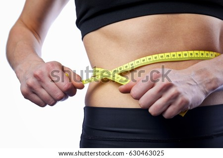 female athlehe measuring waist with measuring tape