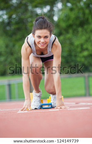 Female athlete at athletic starting blocks on track field - stock photo