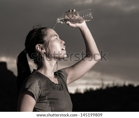 Female Athlete Cooling Off With Water - stock photo