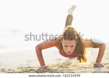 Female athlete doing push ups on beach - stock photo