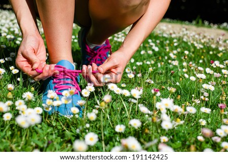 Female athlete getting ready for running in spring park. Fitness workout outdoor concept. - stock photo
