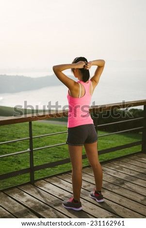 Female athlete getting ready for sport and fitness exercising. Rear view of full body sporty woman looking the sea.