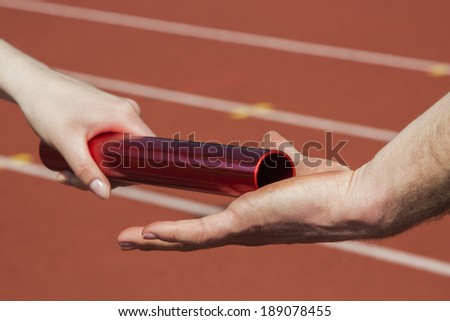 Female athlete hands over the relay race bar to a male athlete - stock photo