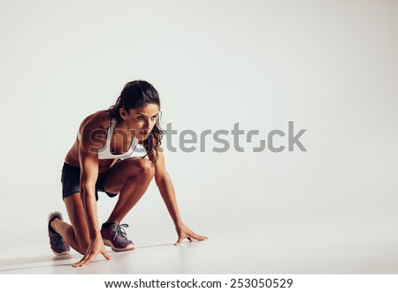 Female athlete in position ready to run over grey background. Determined young woman ready for a sprint. - stock photo