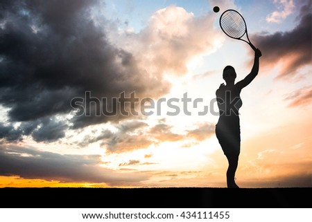 Female athlete playing tennis against blue and orange sky with clouds