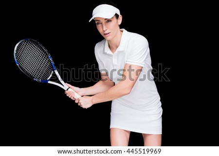 Female athlete playing tennis on black background