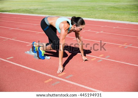 Female athlete ready to run on running track - stock photo