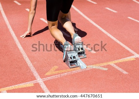 Female athlete ready to run on running track