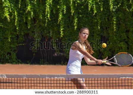 Female athlete returning ball. Young woman playing tennis swinging racket returning ball orange clay ground white dress with miniskirt green fence on background - stock photo