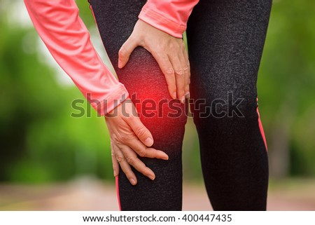 Female athlete runner touching Knee in pain, fitness woman running in summer park. Healthy lifestyle and sport concept - stock photo