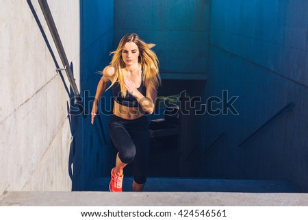 Female athlete running fast up the stairs - staircase workout - stock photo