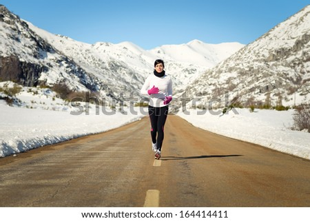 Female athlete running in cold winter mountain road. Woman training for marathon outdoors wearing warm sportswear. - stock photo