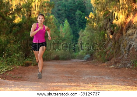 Female athlete running on forest road - copy space. Chinese Asian / Caucasian female woman runner. - stock photo