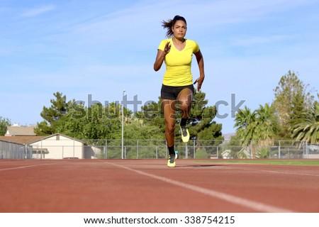 Female Athlete Running on Race Track - stock photo