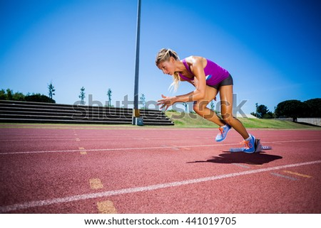 Female athlete running on the racing track on a sunny day - stock photo