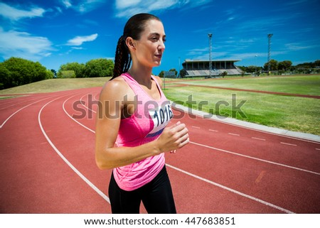 Female athlete running on the running track on a sunny day - stock photo