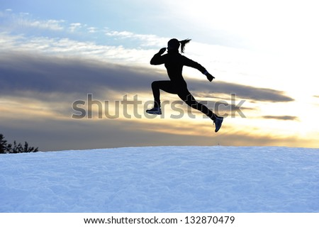Female athlete running outdoors in winter - stock photo