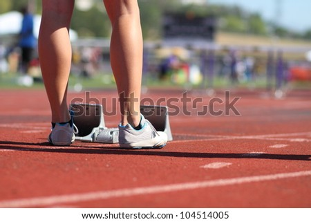 Female athlete sprinter standing behind starting block at the starting line, about to compete in the 100 meter hurdle track & field event. - stock photo