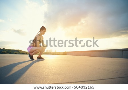 Female athlete squatting near ground outside during early morning sun reaching over city skyline toward park with long shadows