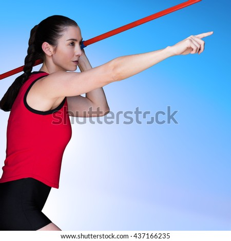 Female athlete throwing a javelin against blue sky
