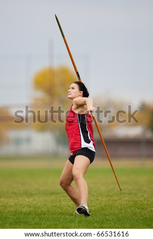 Female athlete throwing a javelin at a track and field sports event - stock photo