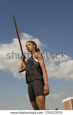 Female athlete throwing javelin - stock photo