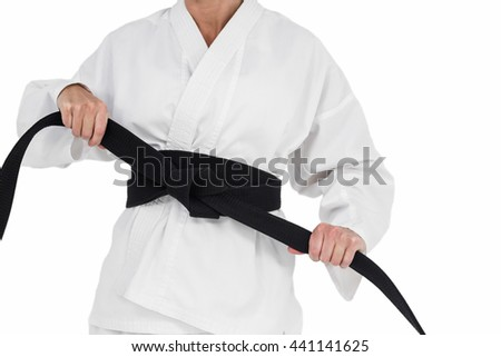Female athlete tightening her judo belt on white background