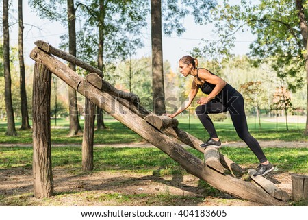 Female athlete training on obstacle course - stock photo