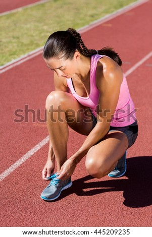 Female athlete tying her running shoes on running track