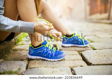 Female athlete tying sport shoes laces for running on tiled pavment in city center. Runner getting ready for training. - stock photo