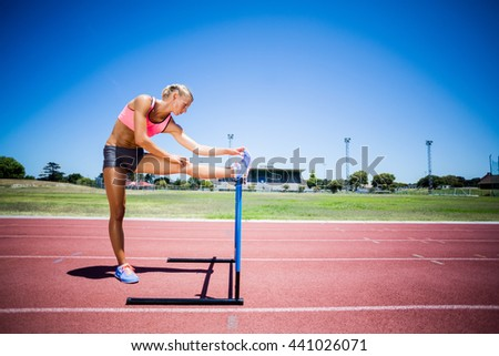 Female athlete warming up on running track on a sunny day